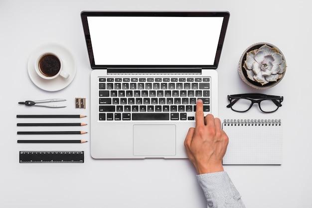 A mão do homem no teclado do laptop sobre a mesa com papelaria de escritório arranjado