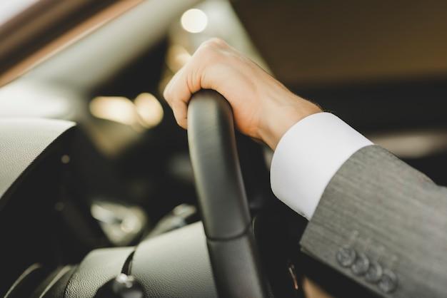 A mão do homem no volante no carro
