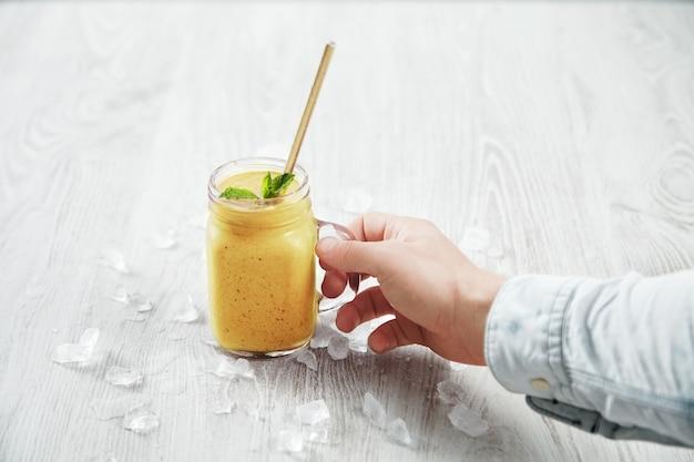 A mão do homem pega um frasco rústico transparente com um saboroso smoothie amarelo de manga feito na hora e saudavelmente