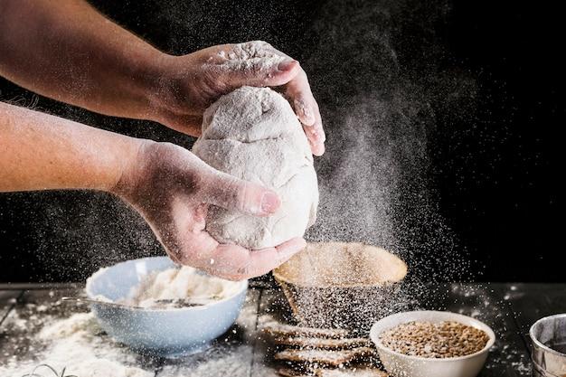 A mão do homem preparando a massa com ingredientes na mesa