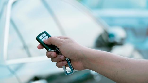 A mão do homem pressiona os sistemas de alarme do carro de controle remoto.