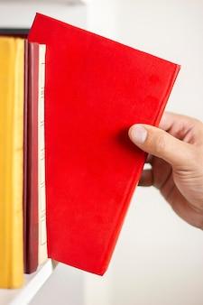 A mão do homem puxa um livro da estante