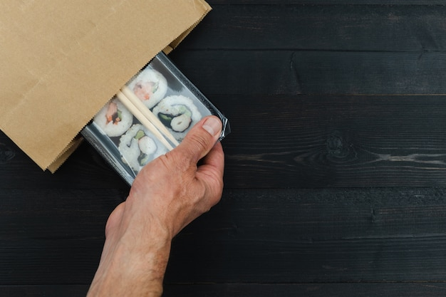 A mão do homem puxando a bandeja de sushi para fora do saco de papel. conceito de comida embalada. copie o espaço.