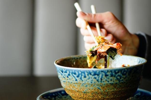 A mão do homem que guarda hashis sobre uma placa da refeição japonesa, tailandesa, chinesa - arroz, cogumelo, vegetais.