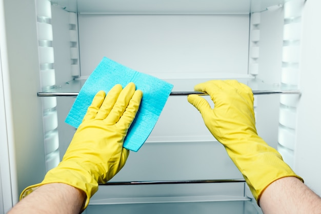 A mão do homem que limpa o frigorífico branco com pano azul