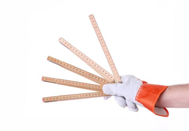 A mão do homem que mantém a ferramenta da construção isolada no branco.