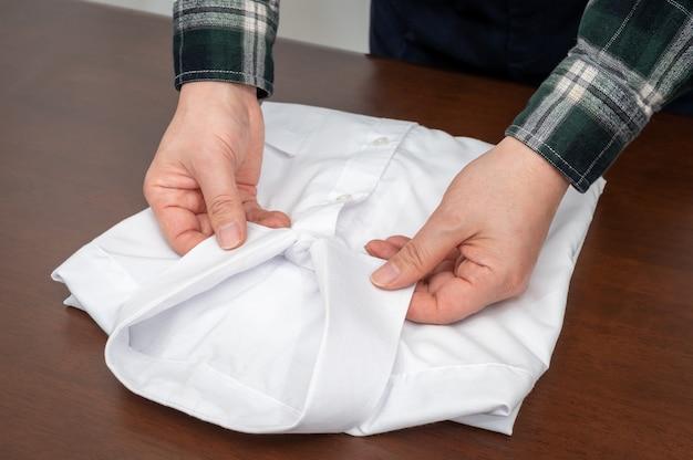 A mão do homem que organiza roupas passadas