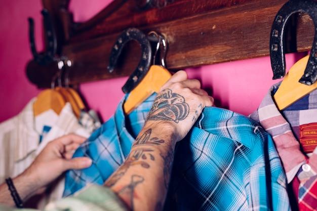 A mão do homem que pendura a camisa xadrez azul no gancho de cabide