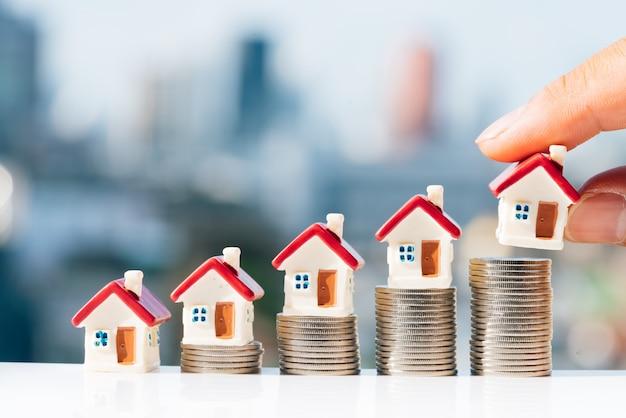 A mão do homem que põe o modelo vermelho da casa sobre a pilha das moedas com fundos da cidade.