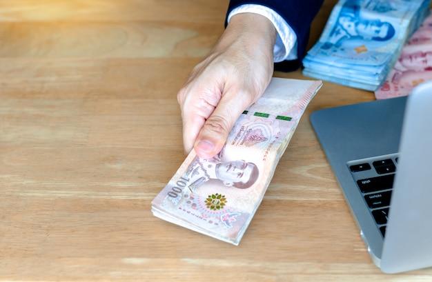 A mão do homem que prende o dinheiro tailandês novo uma cédula de 1.000 bahts.