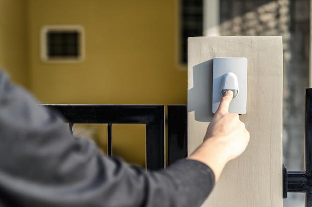 A mão do homem que pressiona um botão da campainha com luz solar.