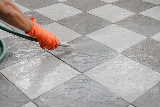 A mão do homem que veste luvas de borracha alaranjadas é usa uma mangueira para limpar o assoalho de telha.
