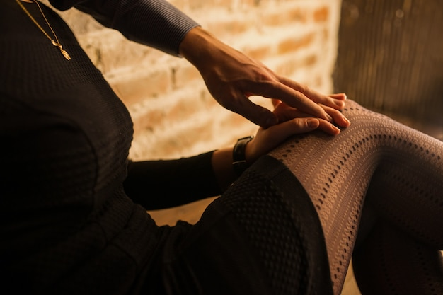 A mão do homem repousa sobre a palma da mão de uma mulher no joelho de uma mulher em uma sala com parede de tijolos e luz quente