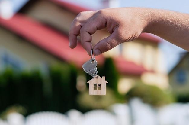 A mão do homem segura as chaves da casa contra o pano de fundo de edifícios residenciais.