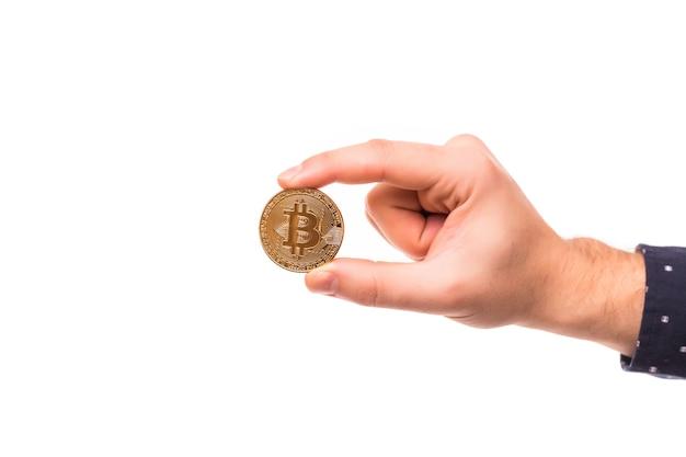 A mão do homem segura um bitcoin de ouro
