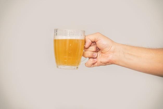 A mão do homem segura uma caneca de cerveja light não filtrada com espuma em um close-up de copo de vidro