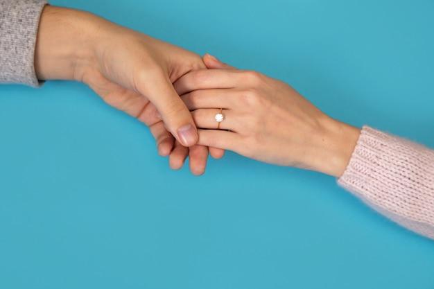 A mão do homem segurando a mão de uma mulher com aliança de casamento em azul.