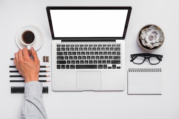 A mão do homem segurando a xícara de café na mesa de escritório com material de escritório arranjado