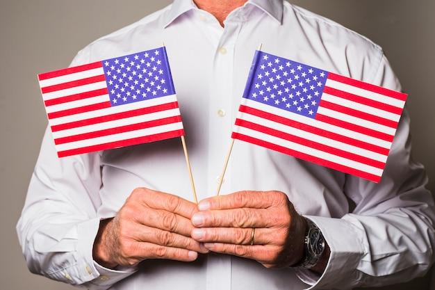 A mão do homem segurando bandeiras eua na mão contra o pano de fundo colorido