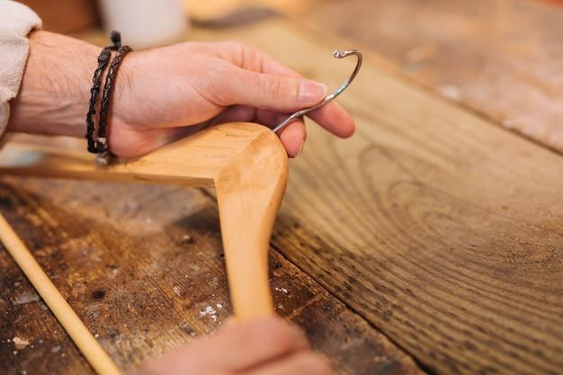 A mão do homem segurando o cabide de madeira na mesa de madeira na loja de roupas