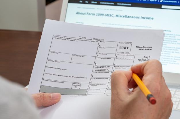 A mão do homem segurando o formulário fiscal 1099-misc.