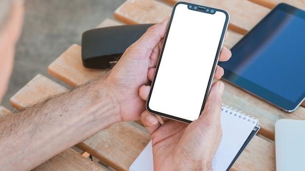 A mão do homem segurando o smartphone com tela branca em branco na mesa de madeira