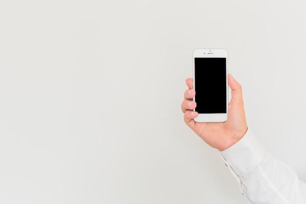 A mão do homem segurando smartphone contra o fundo branco