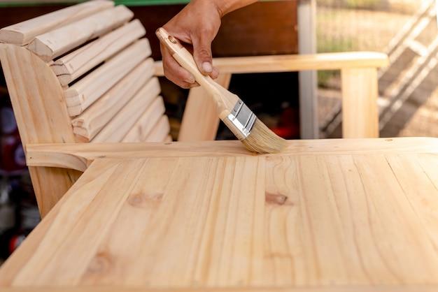 A mão do homem segurando um pincel, aplicando tinta de verniz em um mobiliário de madeira