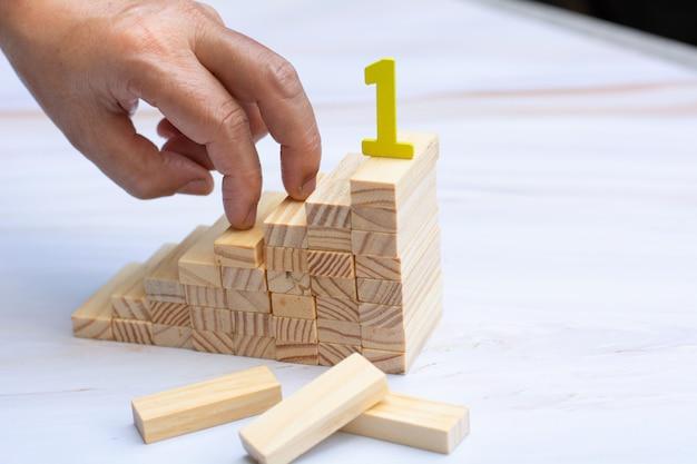 A mão do homem segurando um top de blocos de madeira sobre o bloco de madeira