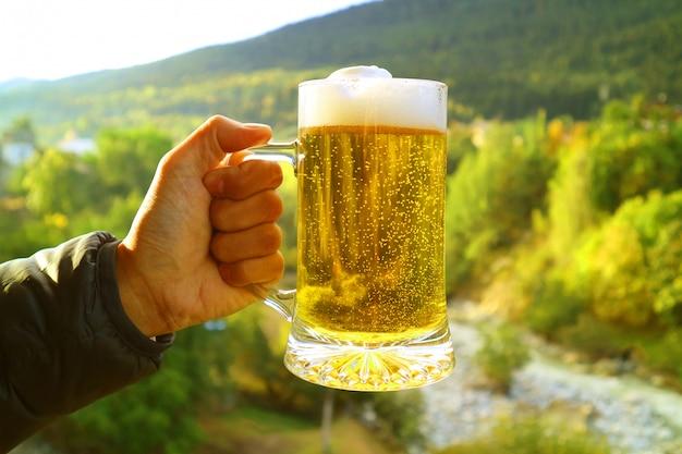 A mão do homem segurando uma caneca de cerveja contra vista para a floresta embaçada sopé na luz solar da noite