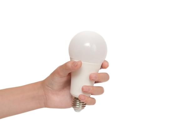 A mão do homem segurando uma lâmpada em um fundo branco
