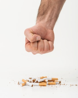 A mão do homem tentando esmagar os cigarros no pano de fundo branco
