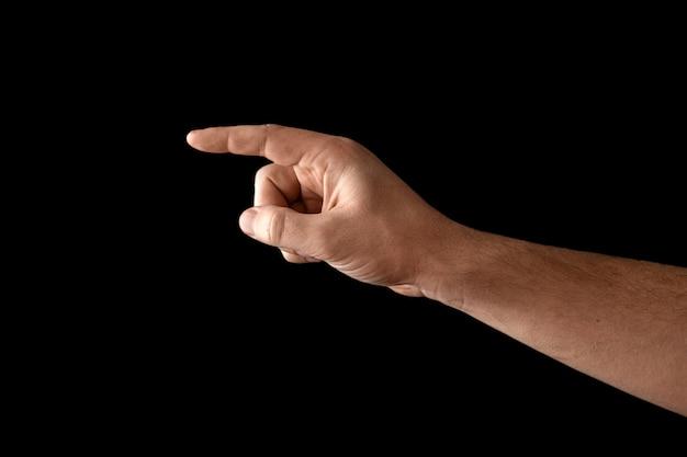 A mão do homem tocando ou apontando para algo isolado no preto