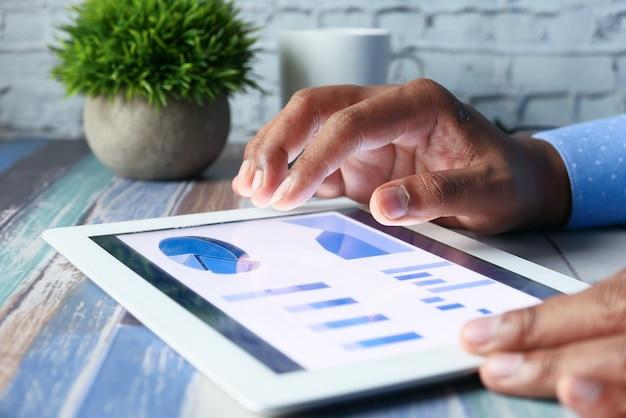 A mão do homem trabalhando em um tablet digital na mesa do escritório, usando um gráfico criado por você mesmo