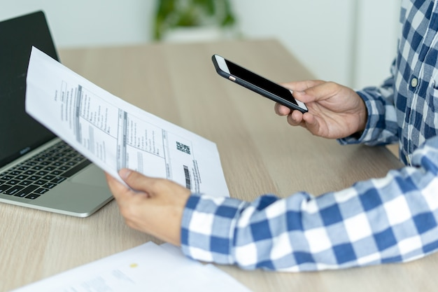 A mão do homem usa um telefone celular para escanear um código de barras ou qrcode com um documento de fatura