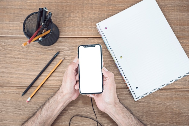 A mão do homem, usando telefone celular na mesa de madeira com artigos de papelaria e caderno espiral