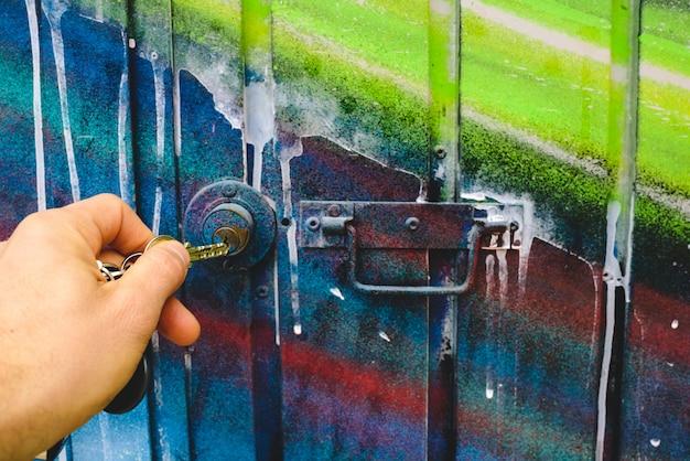 A mão do homem usando uma chave para abrir a fechadura de uma porta de uma garagem abandonada.