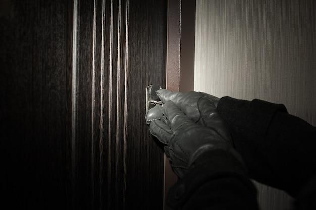 A mão do homem usando uma luva, abrindo a porta