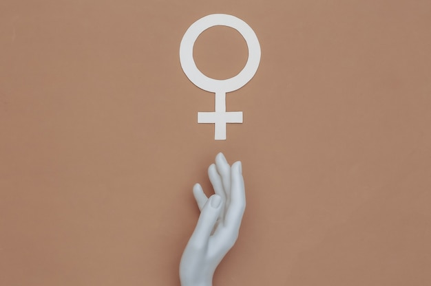 A mão do manequim toca o símbolo do gênero feminino em fundo marrom. vista do topo