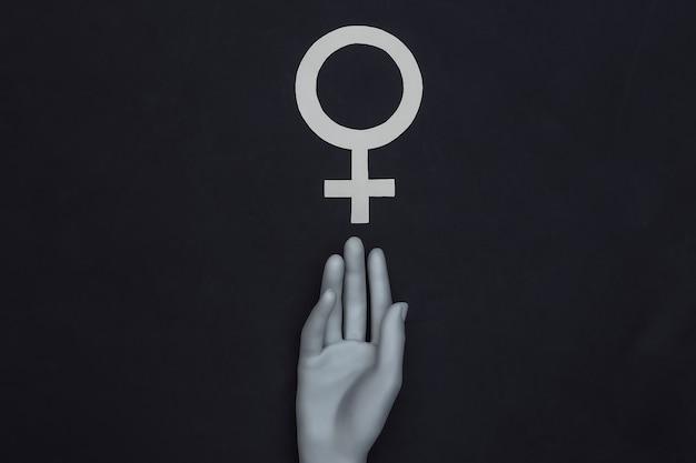 A mão do manequim toca o símbolo do gênero feminino em um fundo preto. vista do topo