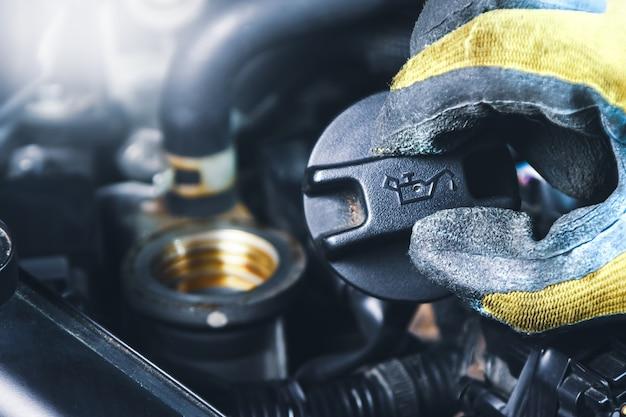 A mão do mecânico abre uma tampa de enchimento de óleo do carro motor