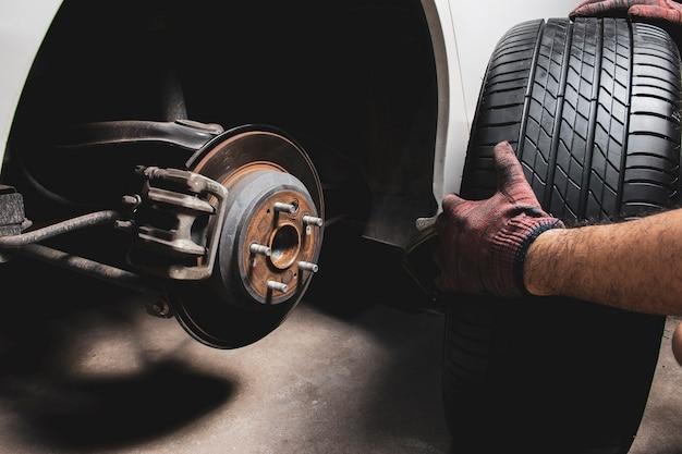 A mão do mecânico segurando pneus pretos para trocar a roda de liga leve no cubo da roda na loja de pneus de carro.