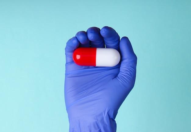 A mão do médico em luvas de látex contém a cápsula sobre fundo azul. conceito médico