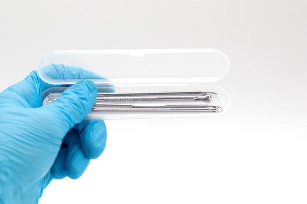A mão do médico em uma luva azul segura um estojo com ferramentas para remoção de acne.