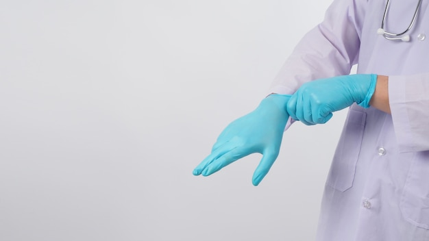 A mão do médico está puxando luvas de látex azuis em fundo branco