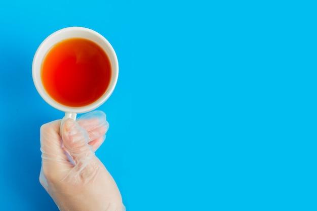 A mão do médico na luva médica mantém a vista superior da xícara de chá branco com copyspace sobre fundo azul
