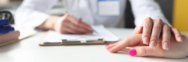 A mão do médico repousa na mão do paciente, o apoio psicológico é fornecido