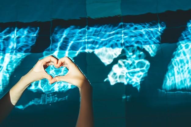 A mão do nadador mergulha em uma piscina de água azul e transparente, na qual a luz do sol brilha