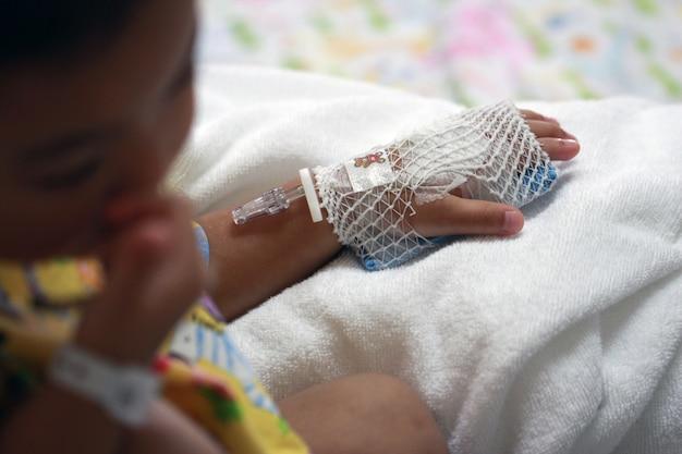 A mão do paciente infantil prepara-se para a solução salina iv no hospital.