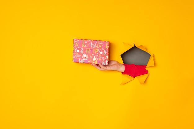 A mão do papai noel segurando uma caixa com um presente no buraco fundo amarelo